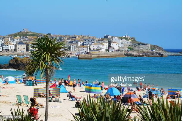 Groups of people relax on the beach in the sun on August 9, 2020 in St Ives, Cornwall, England. The RNLI has called on beachgoers in the south west...
