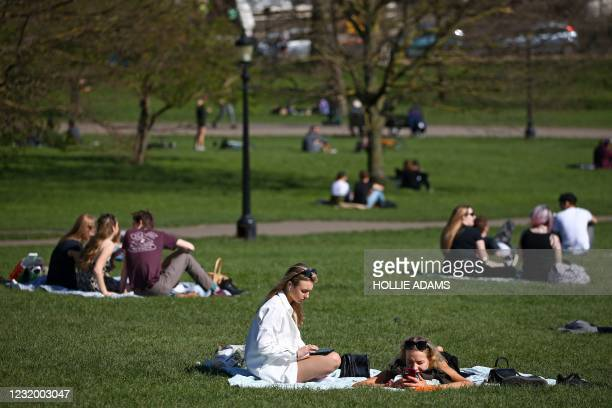 Groups of people sit and chat together in the warm weather on Primrose Hill in London on March 29 as England's third Covid-19 lockdown restrictions...