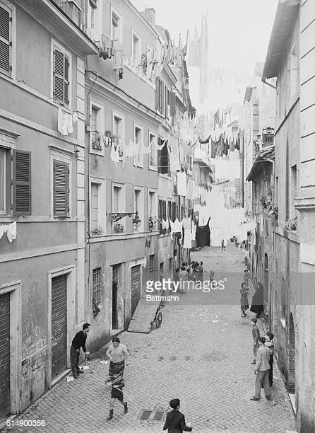 Groups of people socialize and play in a cobblestone alley below their laundry on clotheslines in Trastevere a neighborhood in Rome