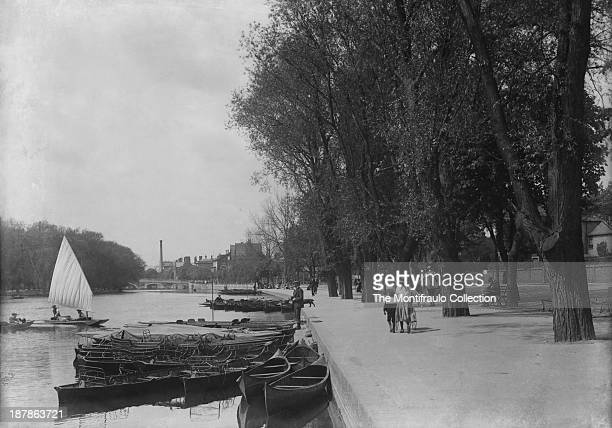 Groups of people some with bikes leisurely walking along the bank of the River Ouse Bedford Bedfordshire England circa 1900