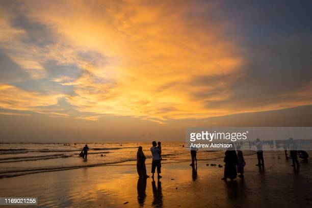 Groups of people stand at the shoreline to admire the dramatic sky at sunset on Laboni Beach Cox Bazar Chittagong Division Bangladesh Asia The wispy...