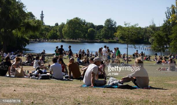 Groups of people sunbathing by the lake in Regent's Park during warm sunny weather on June 01, 2020 in London, UK. The British government further...
