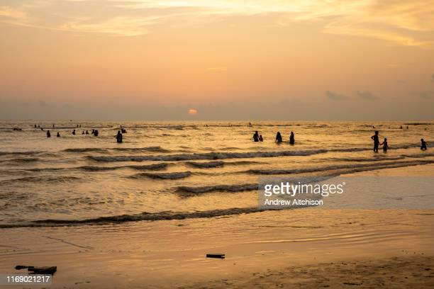 Groups of people swimming in the Bay of Bengal sea during sunset on Laboni Beach Cox Bazar Chittagong Division Bangladesh Asia The sun is setting...