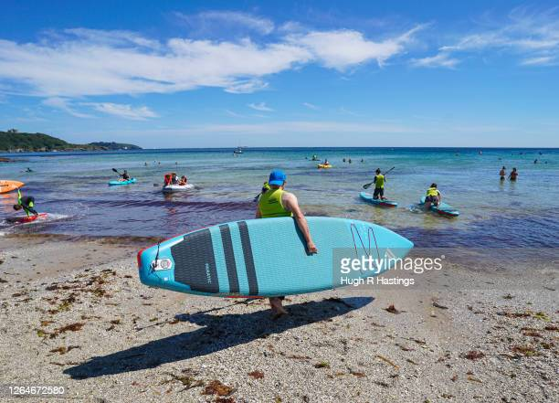 Groups of people take out paddle boards on Gyllyngvase Beach on August 8 2020 in Falmouth Cornwall England The RNLI has called on beachgoers in the...