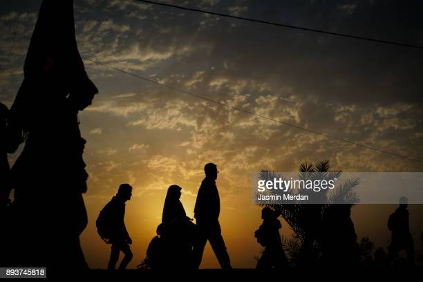 groups of people walking at sunset - イラク ストックフォトと画像