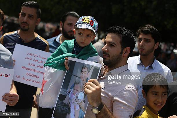 Groups of Syrian refugees hold slogans during a protest against Syrian President Bashar alAssad in gaza city May 1 2016 At least 34 people were...