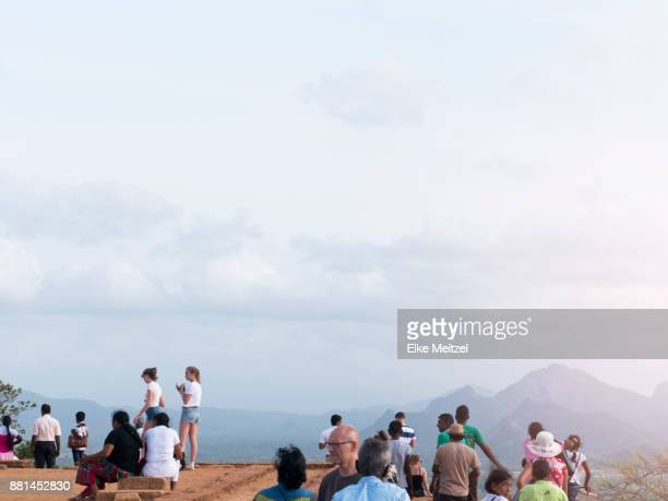 groups of tourists at the top of the ancient site of Sigiriya