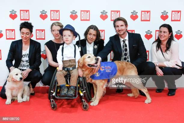 Groupshot with German presenter Dunja Hayali with an assistance dog puppy Robin Richter and Vita founder Tatjana Kreidler with an assistance dog...