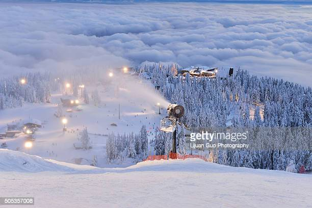 grouse mountain ski hill with foggy cityscape beneath at sunset - grouse mountain stock photos and pictures
