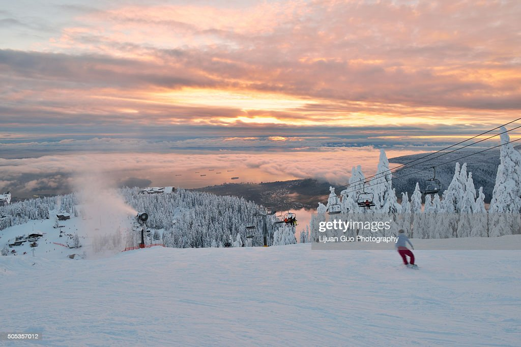 Grouse Mountain Ski Hill with foggy cityscape beneath at sunset : Stock Photo