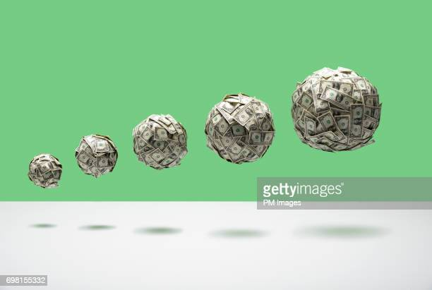 Growing balls of money floating in mid air