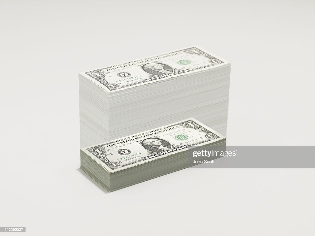 A growing pile of dollar bills : Stock Photo
