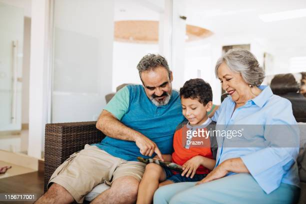 growing up with parents and grandparents in latin america. - family at home stock photos and pictures