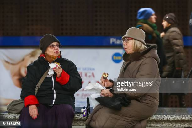 Grown women eating donuts at the subway station during Fat Thursday on February 23 in Warsaw Poland Fat Thursday is a traditional Catholic Christian...