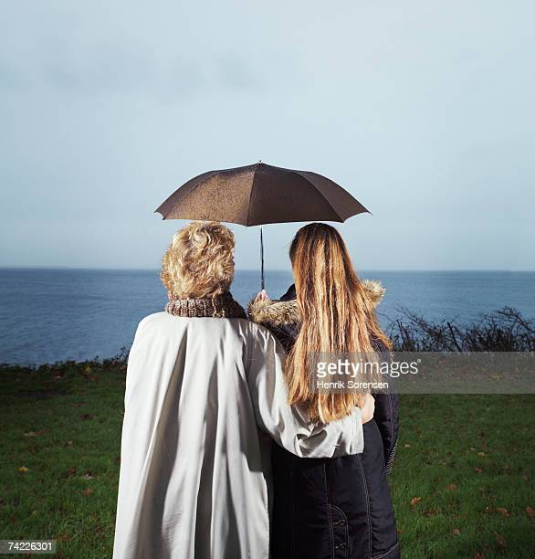 'Grown-up mother and daughter standing under umbrella looking at view, rear view'