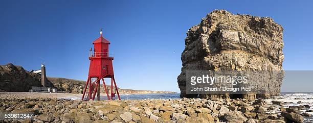 Groyne lighthouse beside a rock formation along the shoreline
