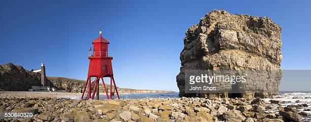 Groyne lighthouse beside a rock formation along the shoreline; South Shields, Tyne and Wear, England