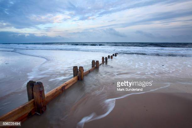Groynes and receding tide on Alnmouth Beach at dusk, Northumberland, England, United Kingdom, Europe