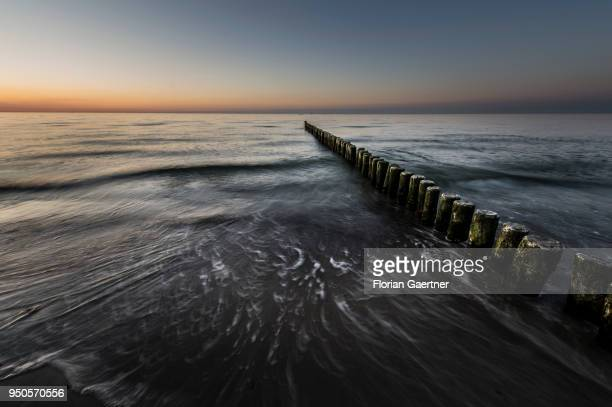 Groynes are pictured after sunset on April 21 2018 in Warnemuende Germany