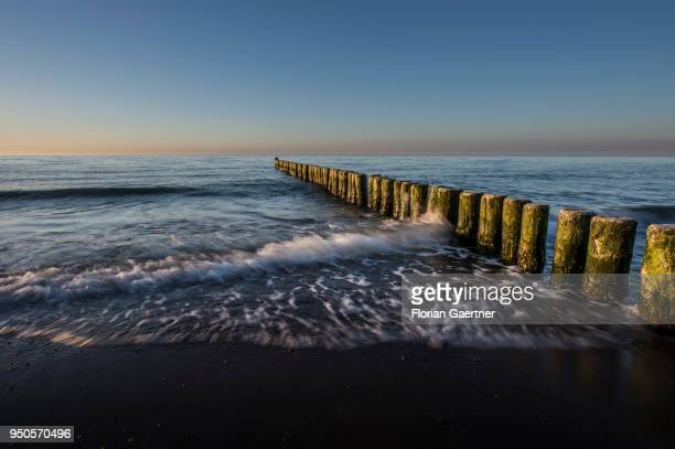 Groynes are pictured during sunset on April 21 2018 in Warnemuende Germany