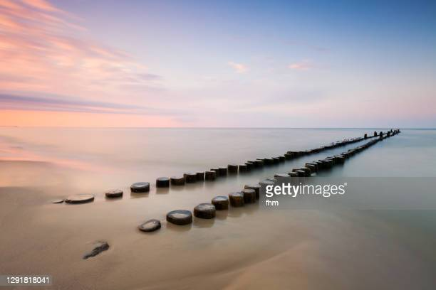groynes on the beach at sunset - water's edge stock pictures, royalty-free photos & images