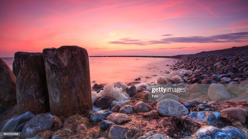 Groynes on the beach in a colorful sunset : Stock Photo