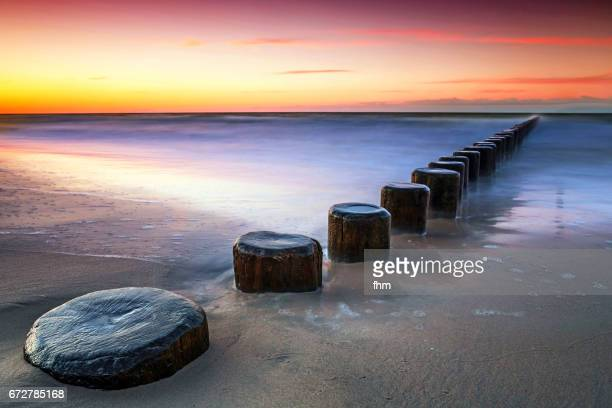 Groynes on the beach in a colorful sunset