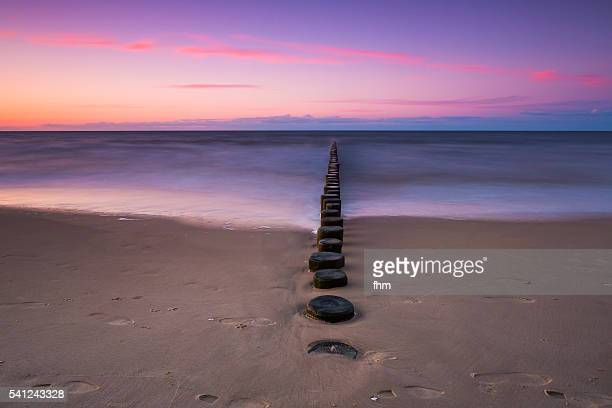 Groynes on the beach in a nice and colorful sunset