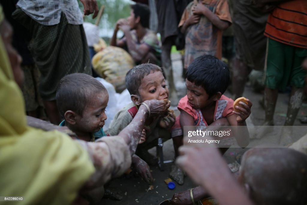 COX'S BAZAR, BANGLADESH - SEPTEMBER 03: A grpup of Rohingya Muslims, fled from ongoing military operations in Myanmars Rakhine state eat food after crossing the Bangladesh-Myanmar border while they are on their way to reach a safer place in Cox's Bazar Bangladesh on September 03, 2017. Violence erupted in Myanmars Rakhine state on Aug. 25 when the countrys security forces launched an operation against the Rohingya Muslim community. It triggered a fresh influx of refugees towards neighboring Bangladesh, though the country sealed off its border to refugees.