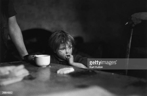 A grubbyfaced child sitting at a sparse dinner table in Wigan Original Publication Picture Post 228 Wigan pub 1939