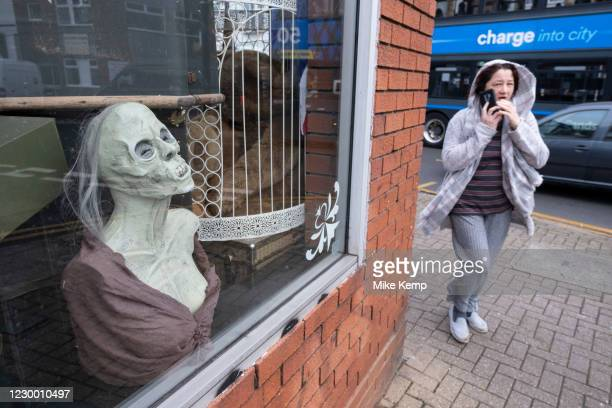Gruesome horror mannaquin in the window as a woman passes by a second hand shop selling all manner of curiosities in Kings Heath on 23rd November...