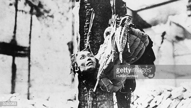 A gruesome picture of victim's head and spoil are strung up on a pole during the Revolution in China 191112