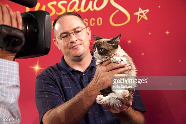 Grumpy Cat is interviewed held by owner Tabatha Bundesen's brother Bryan at Madame Tussauds San Francisco on December 8 2015 in San Francisco...