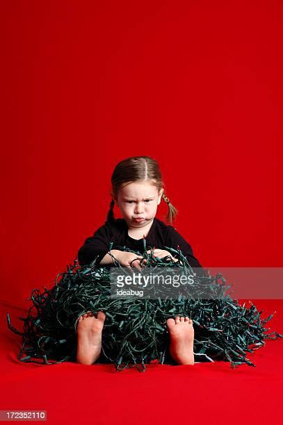 Grumpy kleines Mädchen mit Haufen von Verheddert Christmas Lights