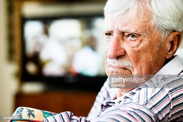 Grumpy old man looks round from television, frowning