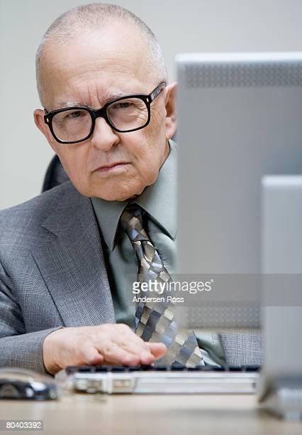 Grumpy senior man sitting at desk