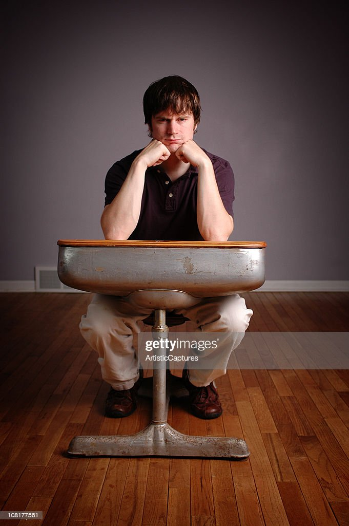 Grumpy Young Man Student Sitting In Old School Desk Stock Photo