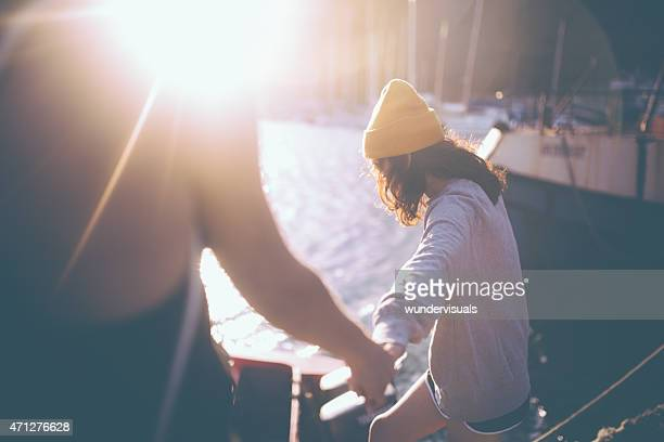 Grunge girl holding hands with her friend with sun flare