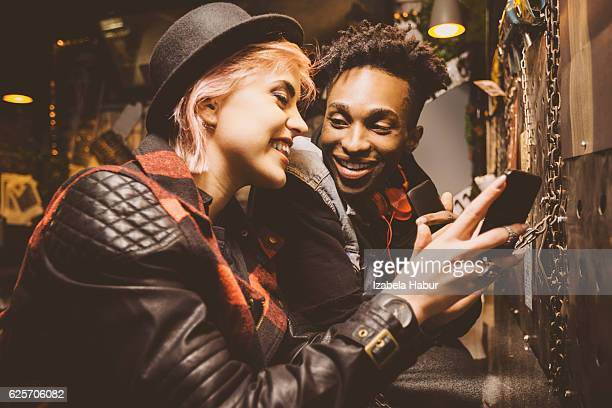 Grunge young couple in a pub, girl using smart phone