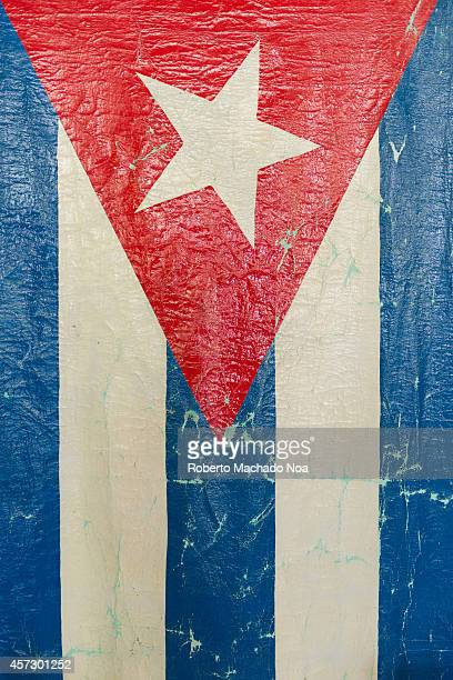 Grungy Cuban Flag The flag of Cuba consists of five blue and white alternating stripes and a red equilateral triangle at the hoist with a white...