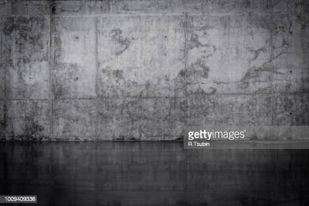 grungy dark concrete wall and wet floor - tranquil scene foto e immagini stock