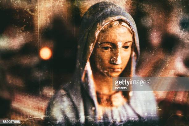Grungy processing of an old and chipped plaster bust of Virgin Mary, one of the iconic figures of some Christian religion.