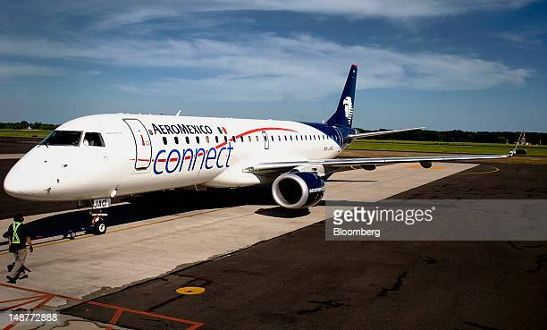 A Grupo Aeromexico SAB Embraer ERJ190100IGW 190AR plane sits by a gate at the Comalapa International Airport in Comalapa El Salvador on Tuesday July...