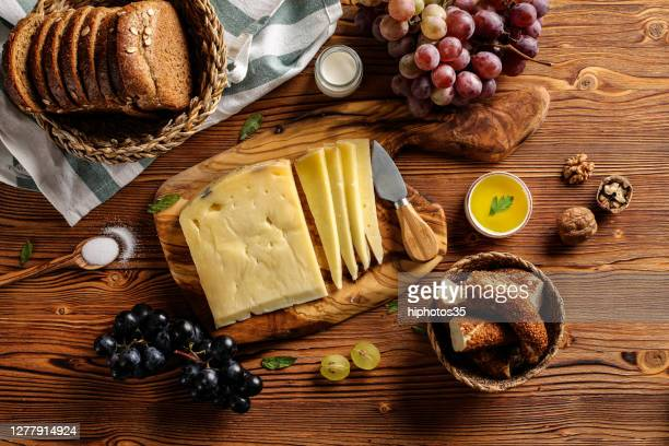 gruyere cheese on wooden table with wooden cutting board, knife and props - high section stock pictures, royalty-free photos & images