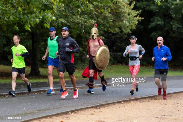 Grzegorz Galezia, a participant of Virgin Money Virtual London Marathon in spartan armorand his supporters are seen running for Spartans for Kids...