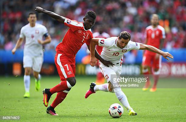 Grzegorz Krychowiak of Poland and Breel Embolo of Switzerland compete for the ball during the UEFA EURO 2016 round of 16 match between Switzerland...
