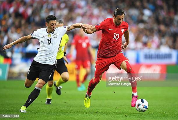 Grzegorz Krychowiak of Poland and Mesut Oezil of Germany compete for the ball during the UEFA EURO 2016 Group C match between Germany and Poland at...