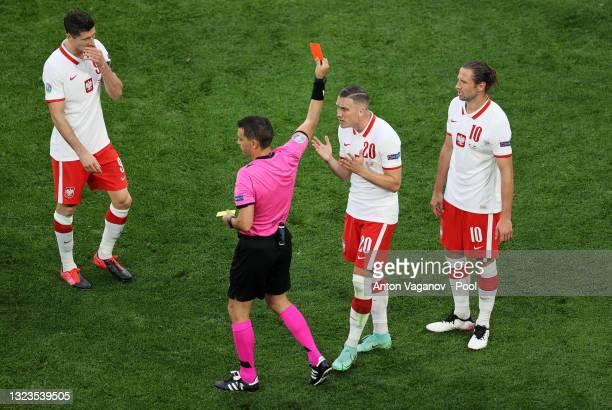 Grzegorz Krychowiak of Poland is shown a red card by Match Referee, Ovidiu Hategan as Piotr Zielinski of Poland protests during the UEFA Euro 2020...