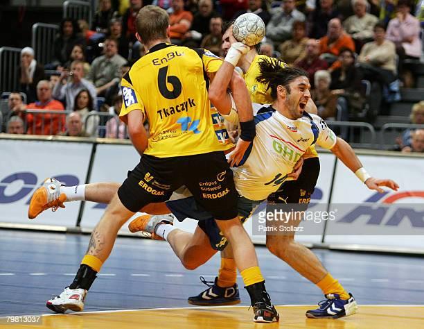Grzegorz Tkaczyk and Sergiy Shelmenko of the Rhein-Neckar Loewen compete with Bertand Gille of Hamburg during the Handball Bundesliga match between...
