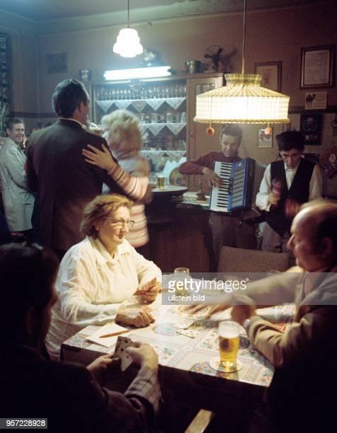 Gäste an einem Tisch in der Kneipe Zum Löwen beim Kartenspiel zwei Musikanten Die lustigen Vagabunden spielen zum Tanz Gemütlichkeit nach Feierabend